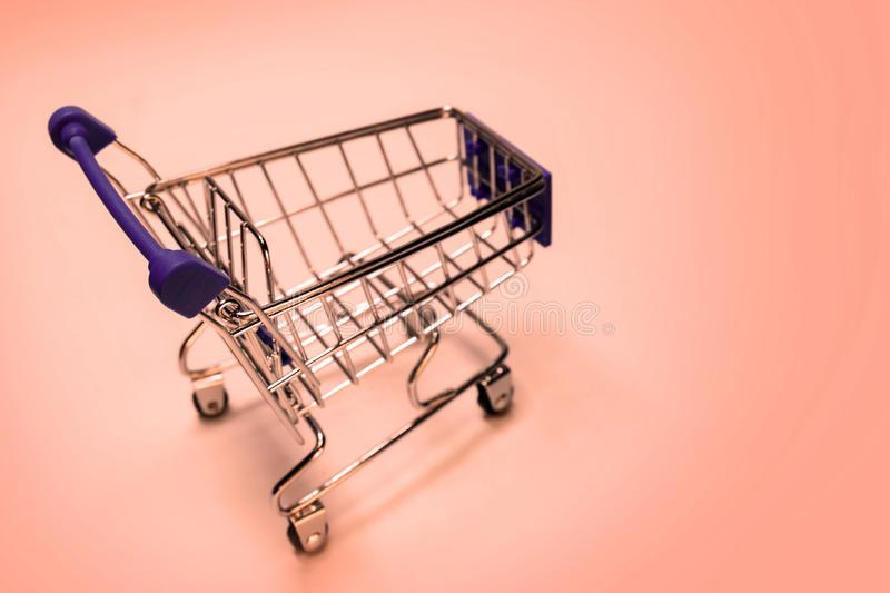 Shopping cart on a pink background. Concept festive sale online, Christmas and New Year discounts, level of consumer basket, black. Shopping cart on a pink stock images