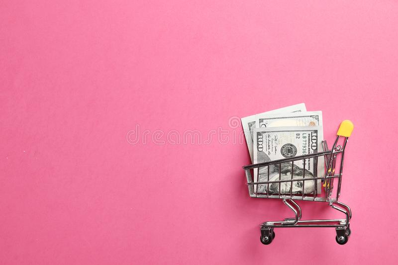 Shopping cart on a pink background. Shopping cart full of money on a pink background with space for text royalty free stock image
