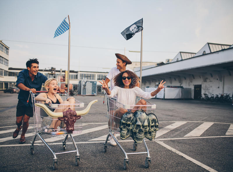 Shopping cart race in parking lot. Multiethnic young people racing with shopping cart. Young friends having fun on a shopping carts in parking lot stock image