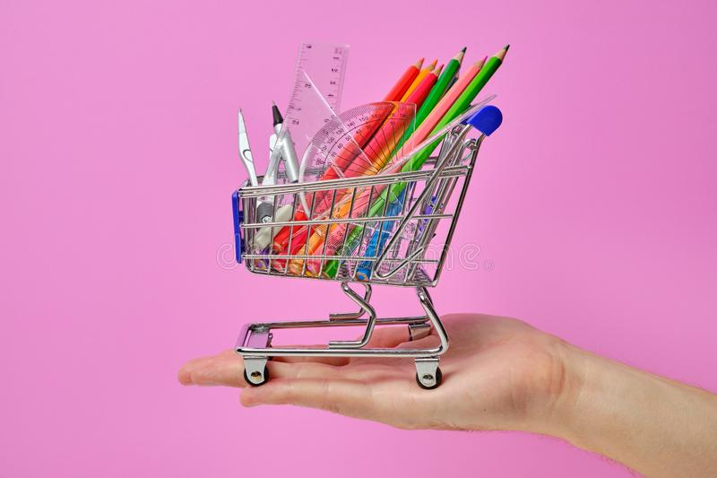 Shopping cart with school staff holding in hand royalty free stock image