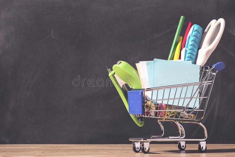 Shopping cart with school supplies over chalkboard background. Back to school sale concept stock photography