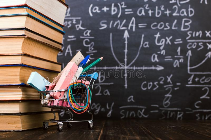 Shopping cart with school supplies, on the table with books against the background of a chalkboard. Concept back to school. Shopping cart with school supplies royalty free stock photography