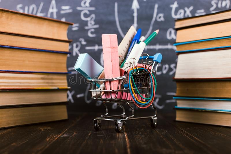 Shopping cart with school supplies, on the table with books against the background of a chalkboard. Concept back to school. Shopping cart with school supplies stock photo