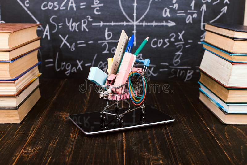 Shopping cart with school supplies, on the table with books against the background of a chalkboard. Concept back to school. Shopping cart with school supplies royalty free stock photos