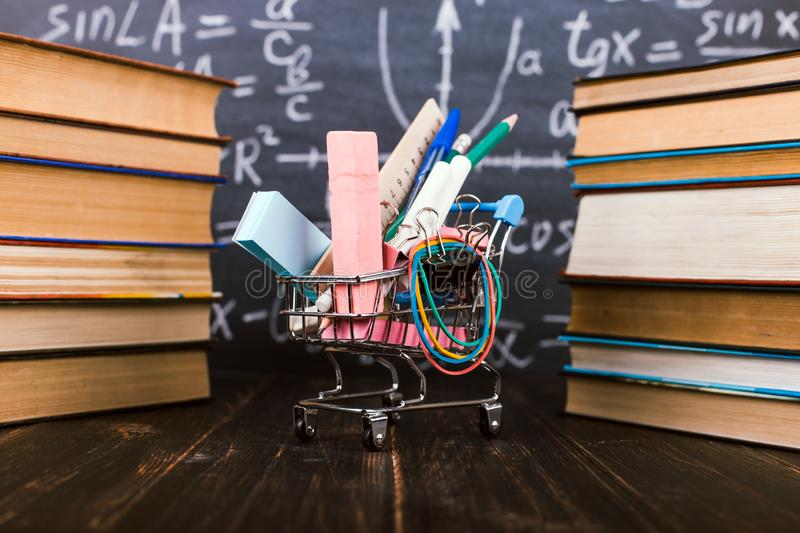 Shopping cart with school supplies, on the table with books against the background of a chalkboard. Concept back to school stock photos