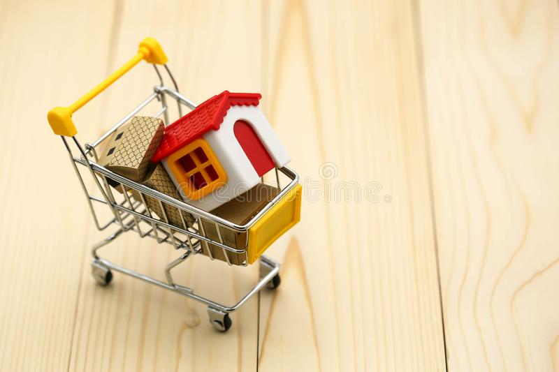 Shopping cart with small house,shopping, rent, loan, mortgage,. Eco district housing concept royalty free stock images