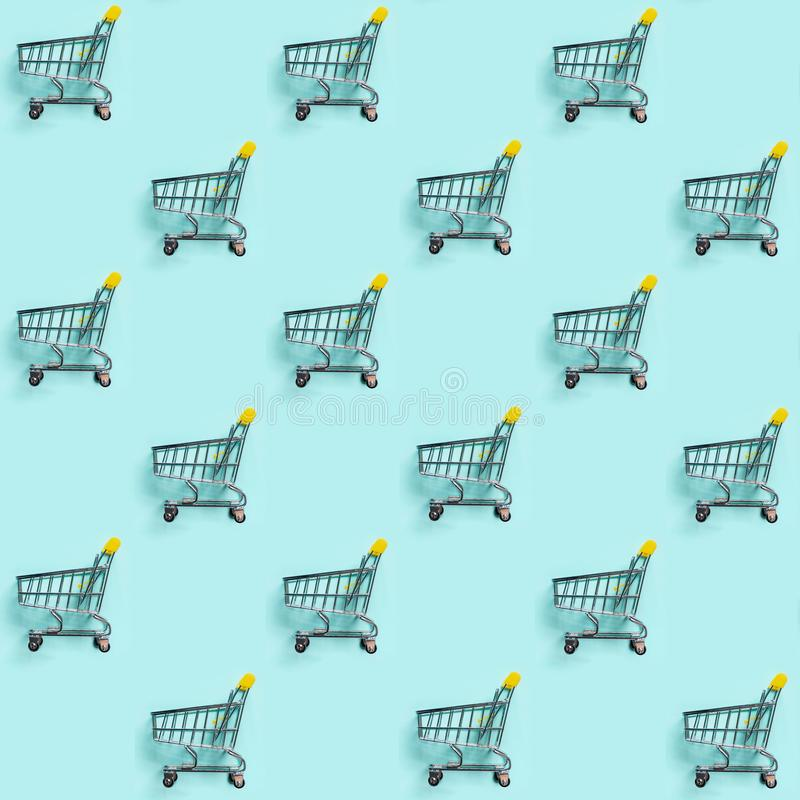 Shopping cart staggered on blue. Seamless pattern royalty free stock photography