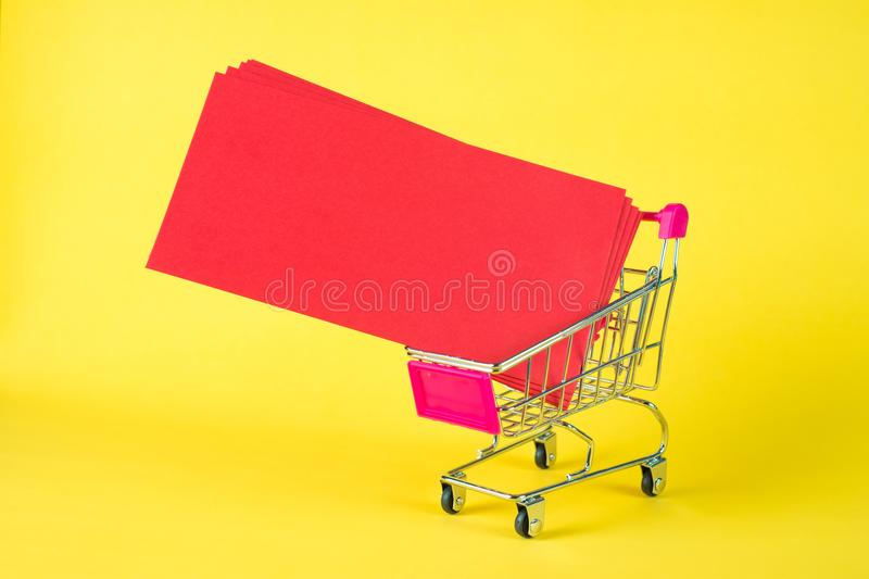 Shopping cart or supermarket trolley and blank red envelop on ye. Llow background with space for add text, Chinese new year and shopping concept idea stock photos