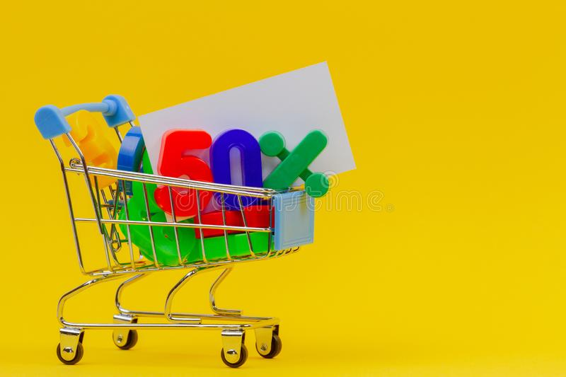 Shopping cart or supermarket trolley with fifty percent sign and full of colorful numbers on yellow background.  stock image