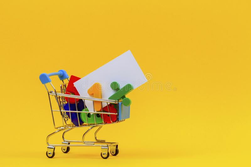 Shopping cart or supermarket trolley full of colorful numbers and white card on yellow background.  stock photos