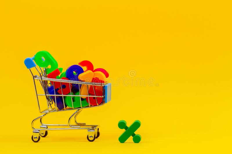 Shopping cart or supermarket trolley full of colorful numbers on yellow background. Shopping cart or supermarket trolley full of numbers on yellow background royalty free stock photography