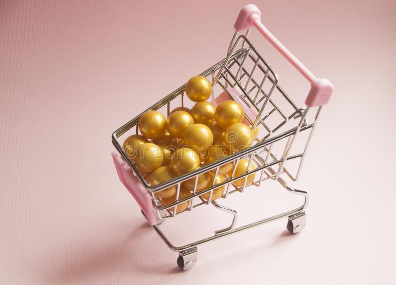 Shopping cart. Supermarket trolley full of golden balls on pink background. Consumerism concept photo. Shopping cart. Supermarket trolley full of golden balls stock photography