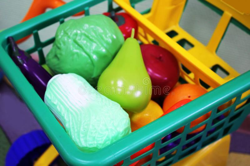Shopping cart trolley full of giant fruits and vegetables. Game royalty free stock photo