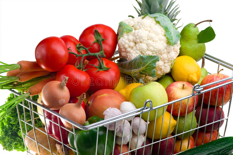 Shopping cart with vegetables. A shopping cart full of fresh colorful vegetables isolated on white background stock images