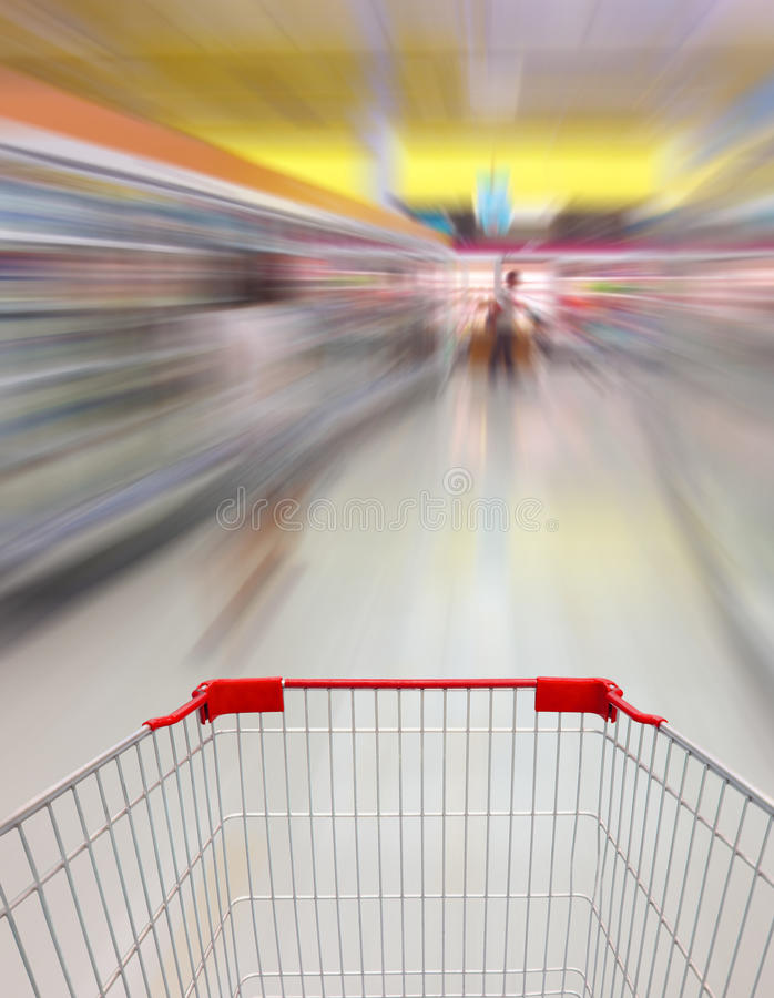 Shopping cart. View in Supermarket Aisle Milk Yogurt Frozen Food Freezer and Shelves blurred background stock photo