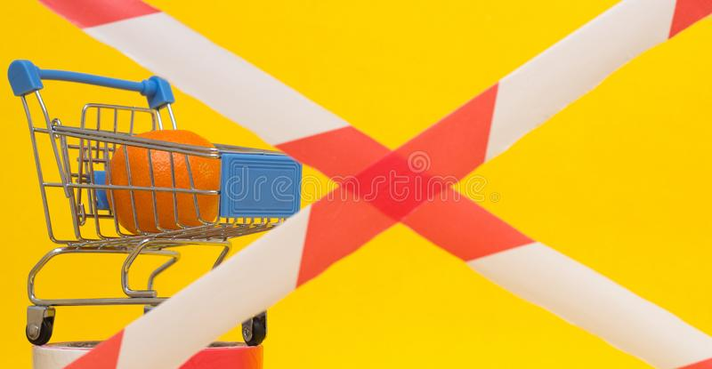 Shopping cart in which lies the mandarin, banned tape, the concept of sanctions on the import of goods and products royalty free stock images