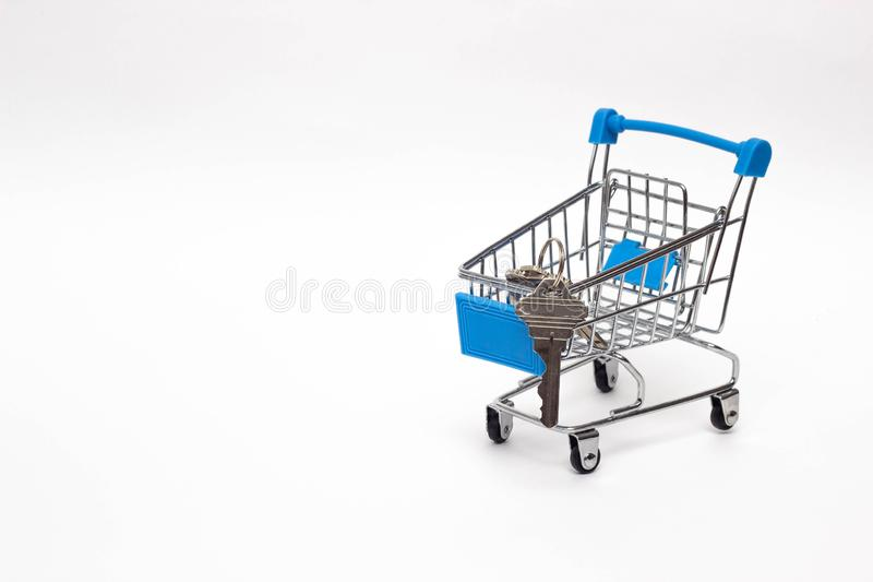 Shopping cart on a white background in which the keys to the apartment, the purchase of real estate, copy space stock photography