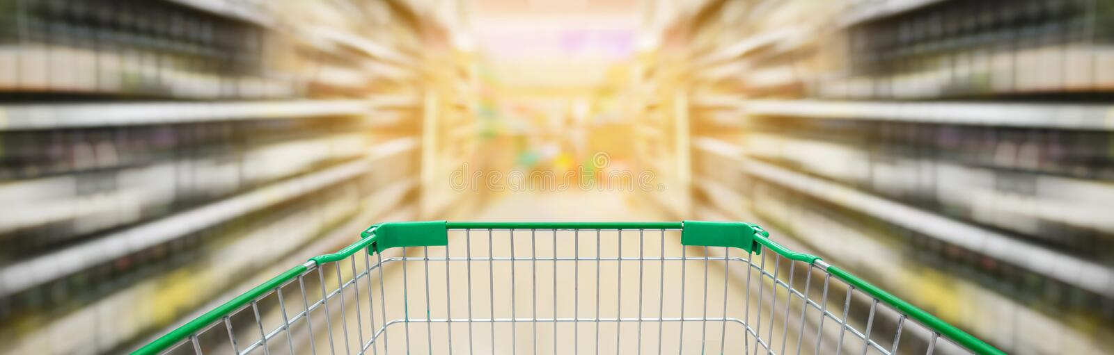 Shopping cart with wine bottles shelves in supermarket aisle royalty free stock photos
