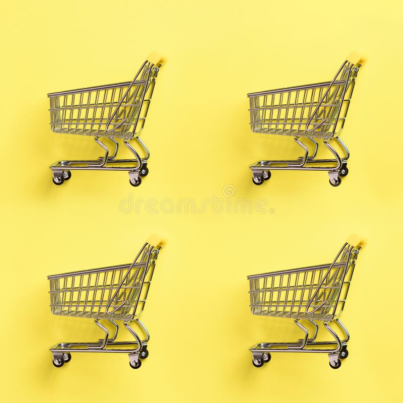 Shopping cart on yellow background. Minimalism style. Creative design. Top view with copy space. Shop trolley at supermarket. Sale. Discount, shopaholism stock photo