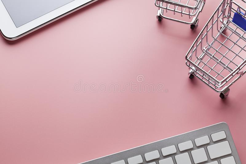 Shopping carts, computer keyboard and modern tablet on pink background stock image