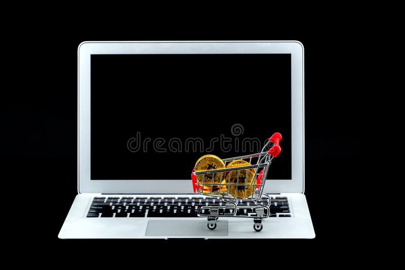 Shopping carts with gold bitcoin on laptop computer isolated on black background stock image