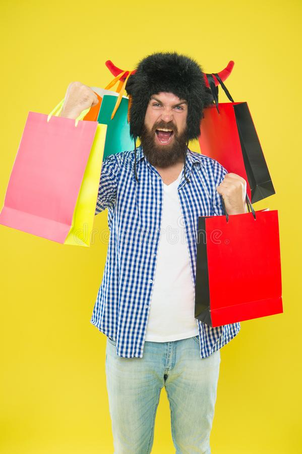 Shopping champion. Happy hipster in bull horns hat holding paperbags after successful shopping. Bearded man smiling with. Shopping bags. Shopping is his royalty free stock photos