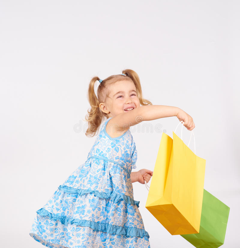 Shopping child. little girl holding shopping bags. On white background stock photography