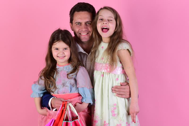 Shopping, childhood and family concept. Sisters and dad share presents royalty free stock photography