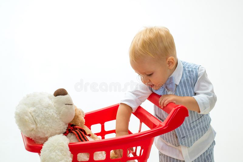 Shopping for children. little boy go shopping with full cart. savings on purchases. happy childhood and care. little boy royalty free stock photography