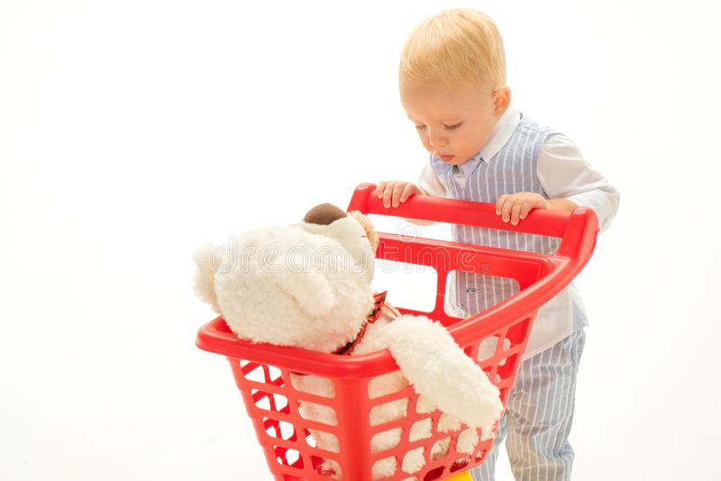 Shopping for children. savings on purchases. little boy go shopping with full cart. little boy child in toy shop. happy royalty free stock photos