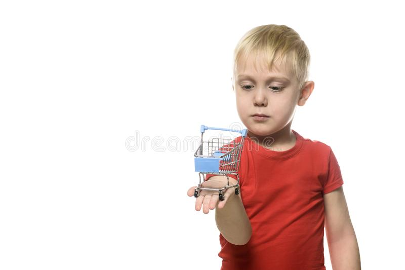 Shopping concept. Blond cute little boy in red t-shirt holding a small metal shopping trolley. Isolate on white background royalty free stock photo