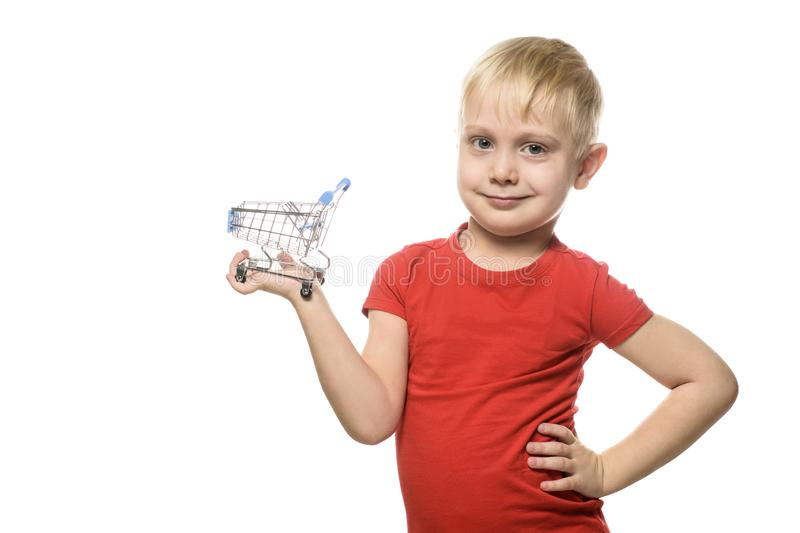 Shopping concept. Blond cute little smiling boy in red t-shirt holding a small metal shopping trolley. Isolate on white background stock photo