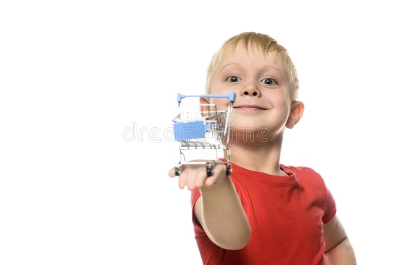 Shopping concept. Blond cute little smiling boy in red t-shirt holding a small metal shopping trolley. Isolate on white background stock images