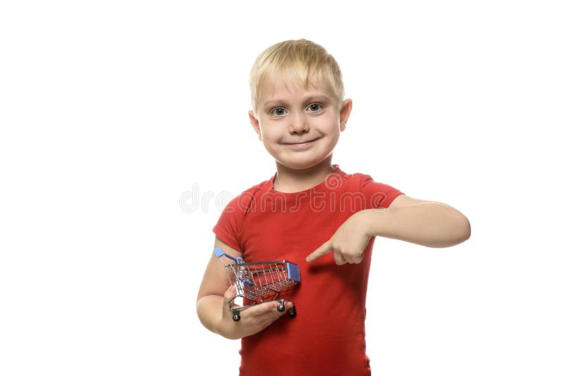 Shopping concept. Blond little smiling boy in a red T-shirt holding a small metal shopping trolley and pointing at it with his royalty free stock photography
