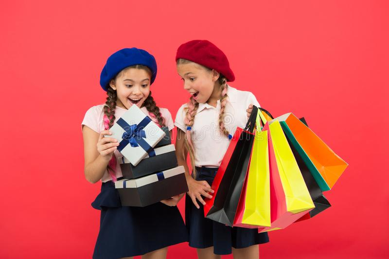 Shopping concept. Child cute small girls on shopping tour. Best price. Buy now. Visit shopping mall. Kids girls hold. Bunch shopping bags or birthday gifts stock photos