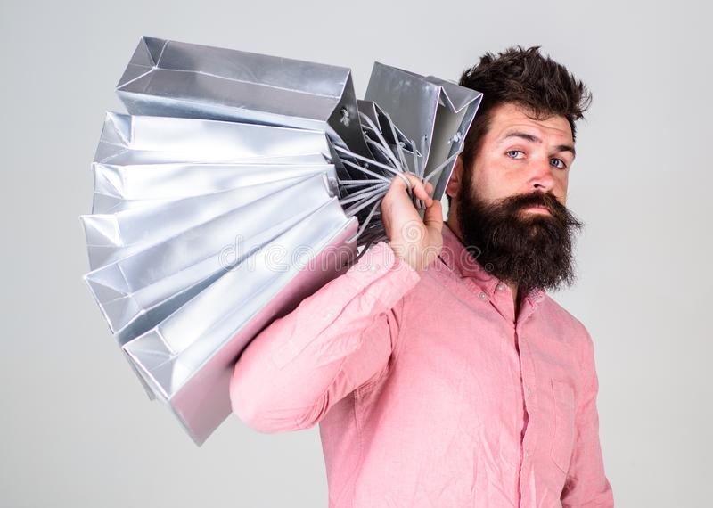 Shopping concept. Guy shopping on sales season, carries bunch of bags on shoulder. Man with beard and mustache holds. Shopping bags, grey background. Hipster on stock photo
