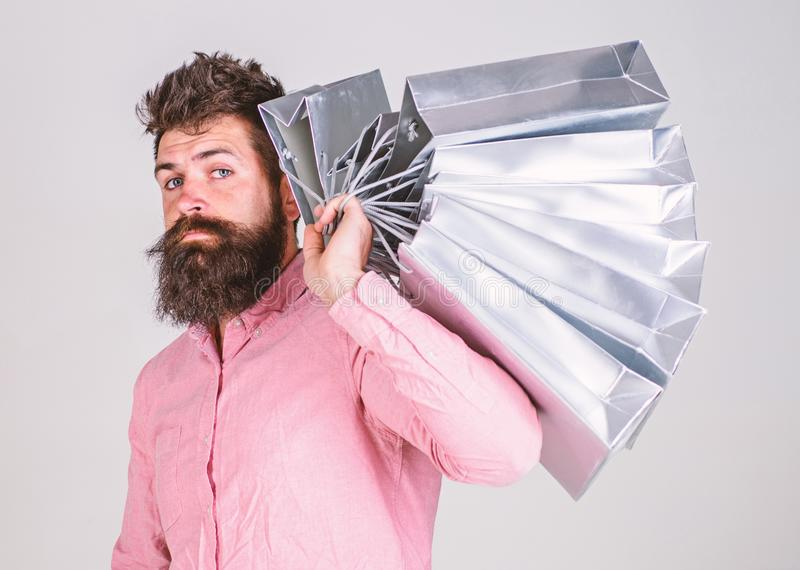 Shopping concept. Guy shopping on sales season, carries bunch of bags on shoulder. Man with beard and mustache holds. Shopping bags, grey background. Hipster on stock image
