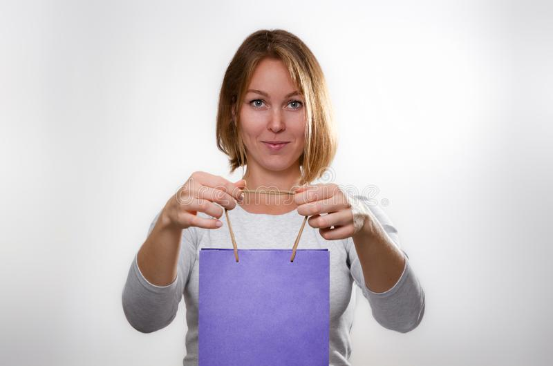 Shopping concept. Portrait of a blonde holding a purple cardboard bag with both hands. White background and copy space stock photo