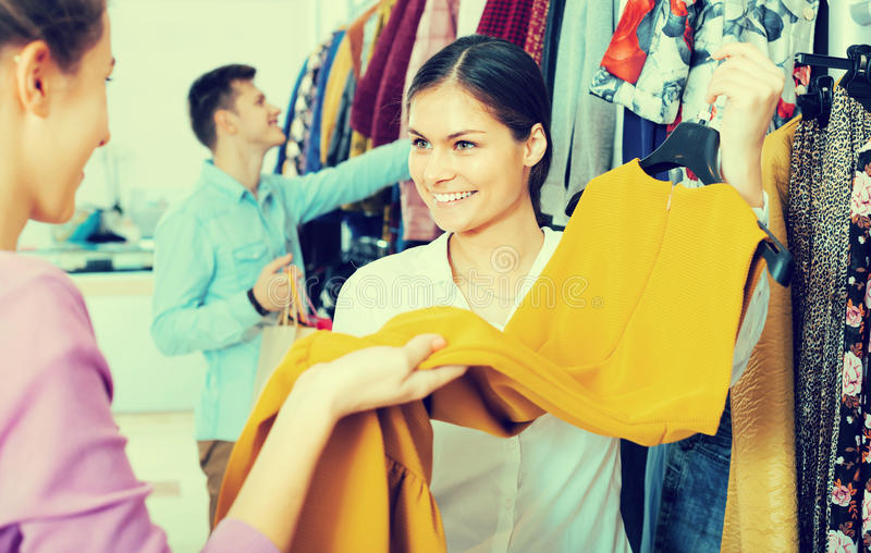 Shopping consultant and client. Smiling female consultant helping girl shopping at apparel store royalty free stock photos
