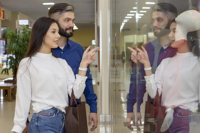 Shopping. A couple examines the window of a boutique with clothes. girl chooses what to buy. sale at the store. stock image