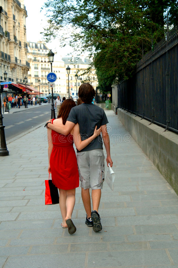 Shopping couple on a Paris street. A young couple walking along a street in Paris with shopping bags stock photography