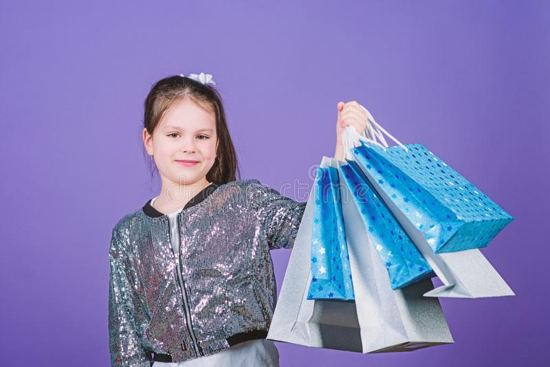 Shopping day. Child hold bunch packages. Kids fashion. Birthday girl. Surprise gift. Girl with shopping bags violet. Background. Shopping and purchase. Get royalty free stock photo