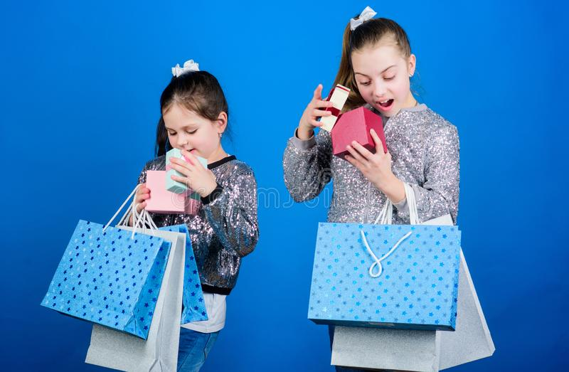 Shopping day. Kids fashion. Girls sisters friends with shopping bags blue background. Every product delivered to you. Shopping and purchase. Black friday. Sale stock images