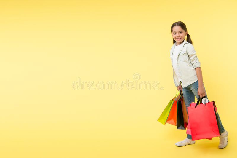 Shopping day. shopping day with happy child. smiling little girl on shopping day. girl with packages after shopping day royalty free stock photos