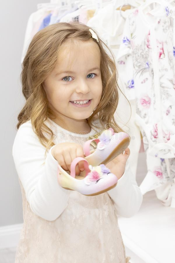 Shopping. discounts. little girl shopaholic. girl chooses shoes for her dress. shopping center, shopping. royalty free stock photo