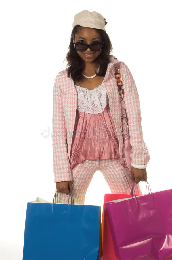 Shopping Diva. Young African American woman Holding colorful shopping bags and looking over her sunglasses stock photo