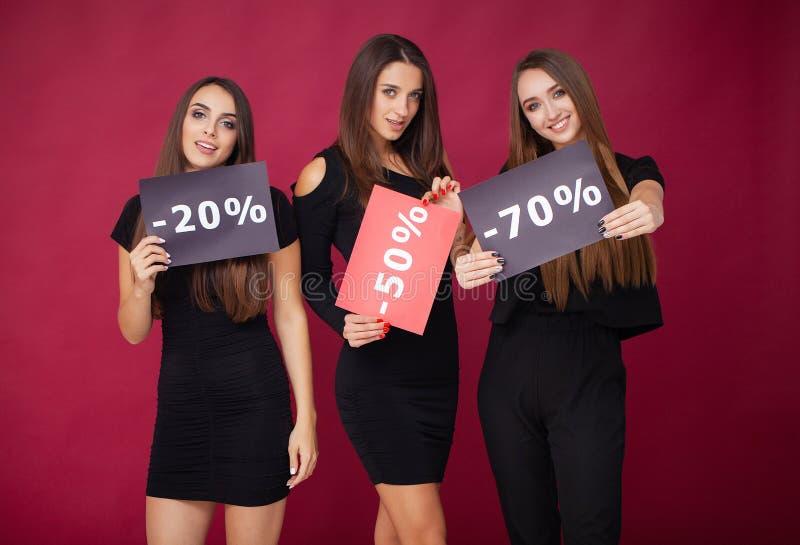 shopping Eleganta brunettkvinnor bär den svarta klänningen som rymmer shoppingpåsar, det svarta fredag begreppet royaltyfria bilder