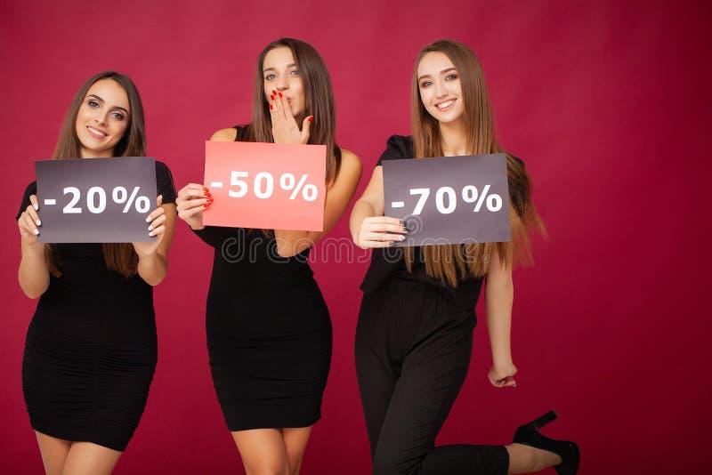 shopping Eleganta brunettkvinnor bär den svarta klänningen som rymmer shoppingpåsar, det svarta fredag begreppet arkivfoto