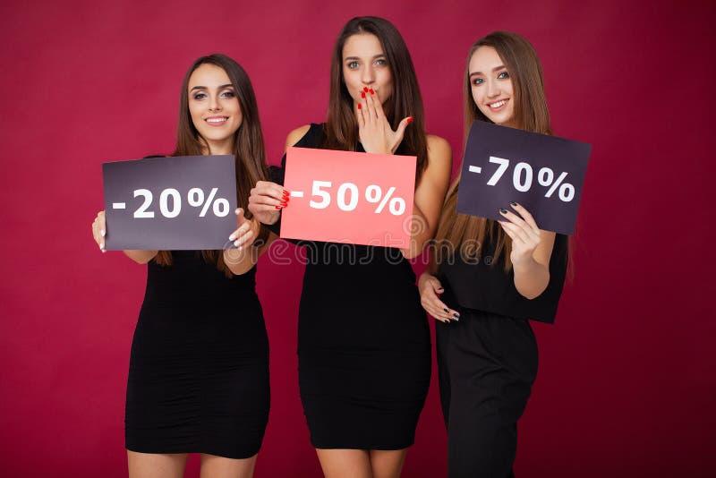 shopping Eleganta brunettkvinnor bär den svarta klänningen som rymmer shoppingpåsar, det svarta fredag begreppet royaltyfri bild