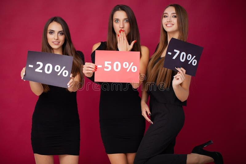 shopping Eleganta brunettkvinnor bär den svarta klänningen som rymmer shoppingpåsar, det svarta fredag begreppet arkivfoton